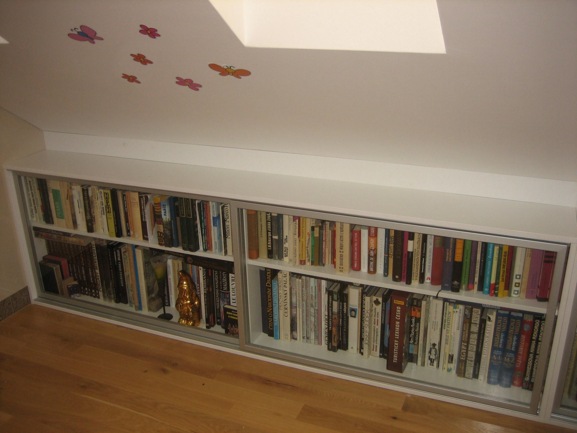nízká knihovna v šikmém podkroví